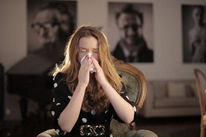 Dziewczyna kichająca w chusteczkę