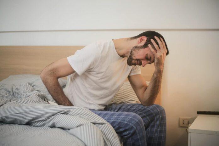 mężczyzna siedzący na lóżku