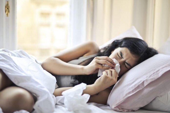 Leżąca w łóżku dziewczyna z katarem