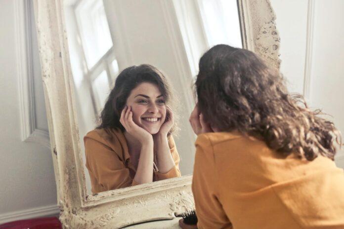 kobieta patrząca na siebie w lustrze