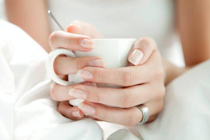 kobiece dłonie trzymające kubek
