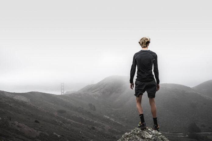 Mężczyzna stojący na szczycie gór